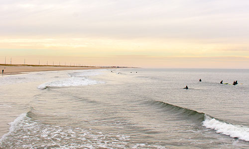 Surfers enjoying the waves at Delaware Seashore State Park