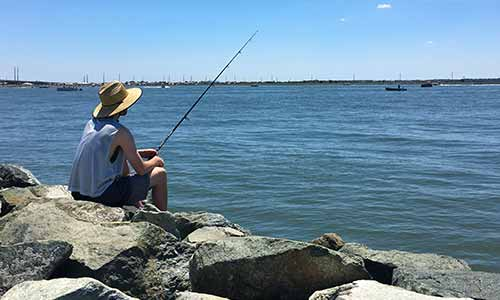 Person fishing off the jetty at Indian River Marina