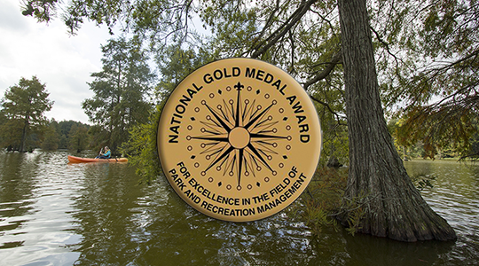 Gold Medal seal in front of people kayaking on a pond