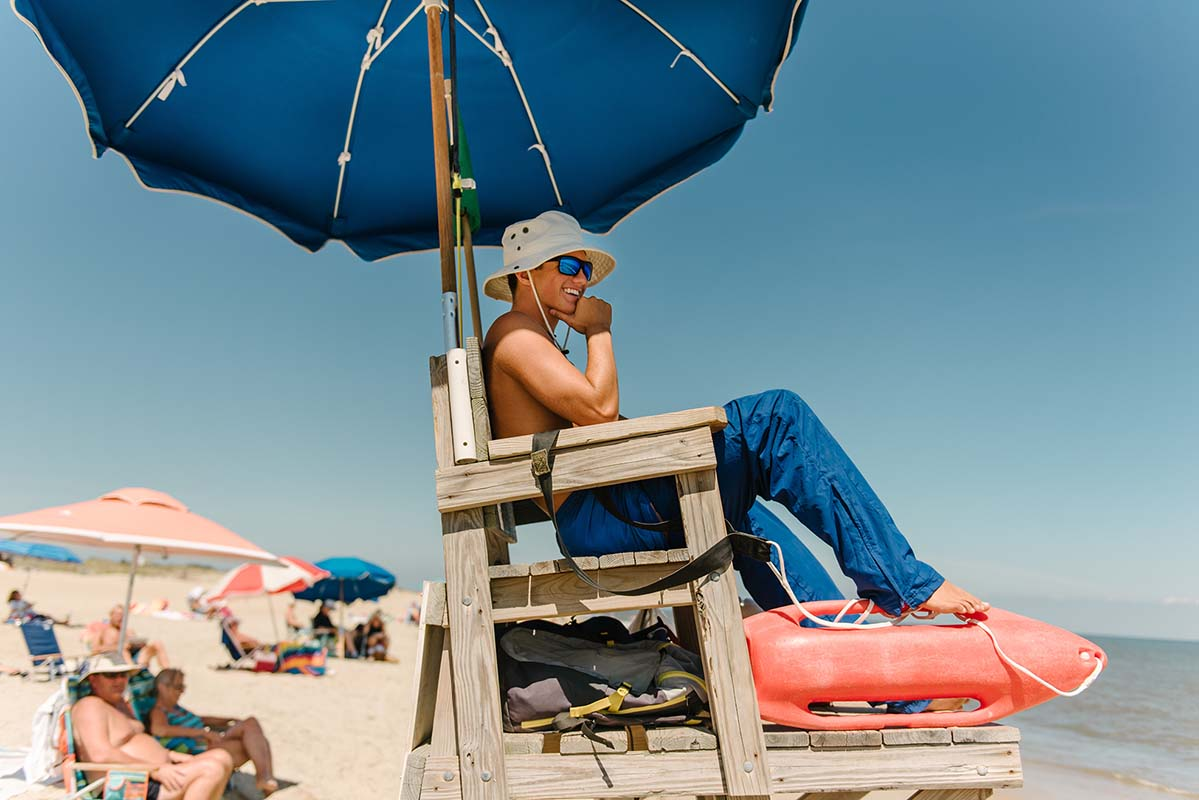 "266b4c4de9e4 lifeguard standing in water at the beach. """