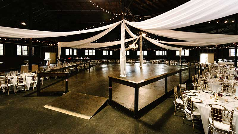 interior of barn decorated for wedding with white streamers