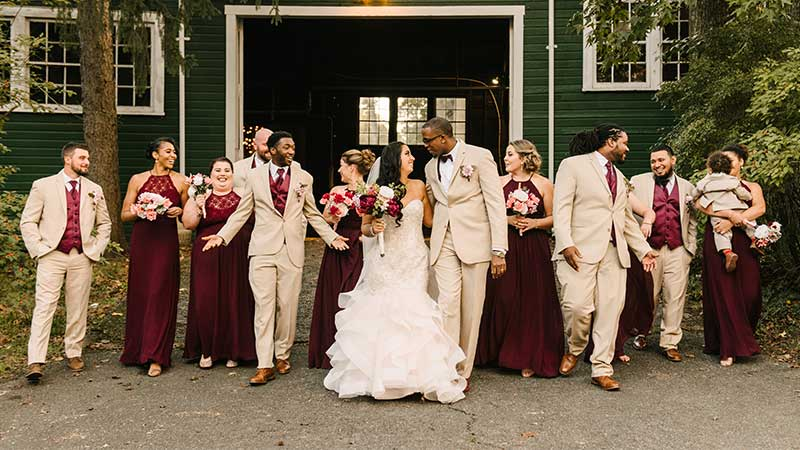 full wedding party in front of barn
