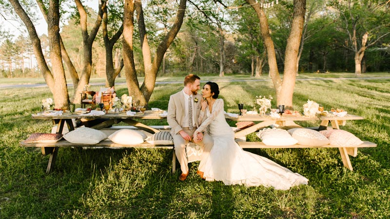 bride and groom sitting at a picnic table