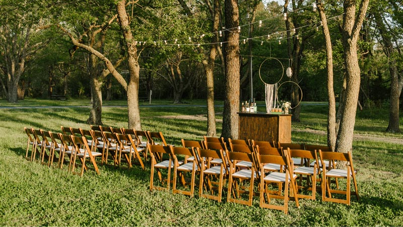 empty wooden folding chairs set up for an outdoor wedding