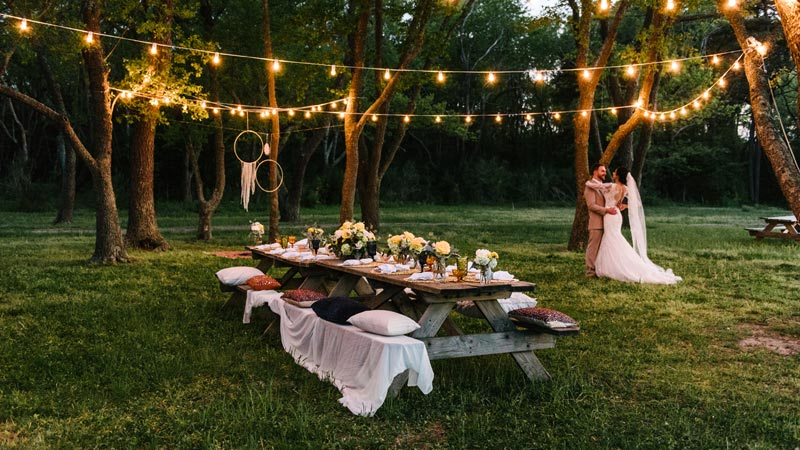 table with wedding place setting and string lights above it