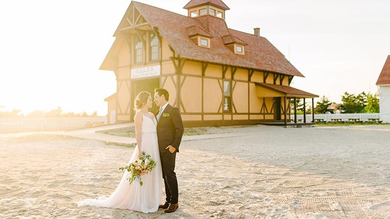 bride and groom in front of life saving station with sun glaring behind them