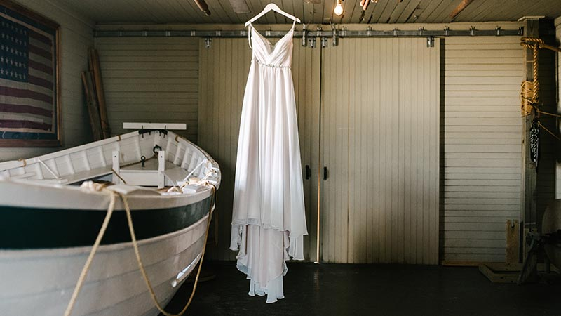 wedding dress hangin up next to a boat inside the life saving station