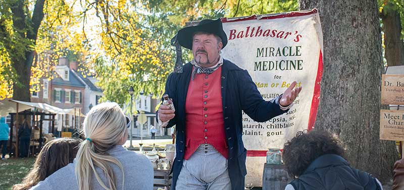 man dressed in 1700s clothes enacting medicine sales