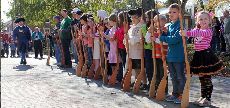people lined up in mock military drill with wooden rifles