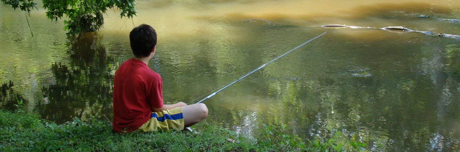 Boy sitting on the banks of Brandywine Creek with a fishing pole
