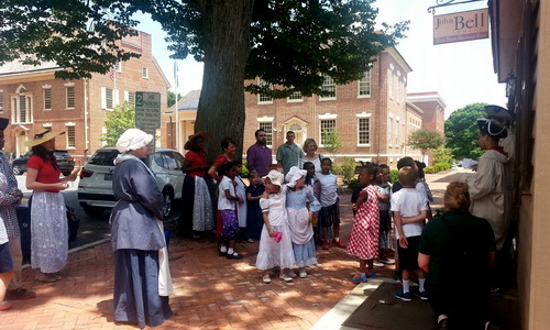 colonial dressed tour guides and group on sidewalk in front of John Bell house