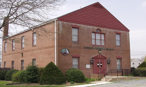 exterior view of Johnson Victrola museum. It's a large 2 story building with a red roof and red front door