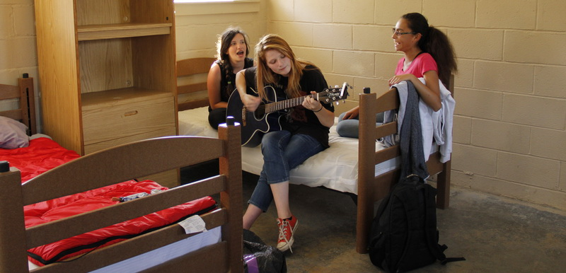 lady playing guitar and two girls singing inside the youth group camping bedroom